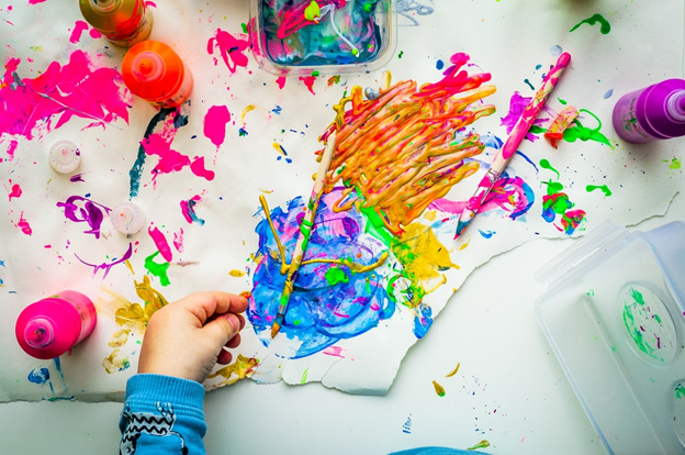 a kid is painting in a preschool