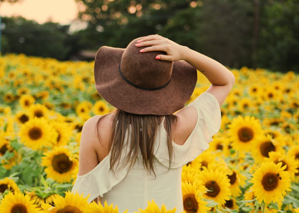 a girl in the sunflower field posing in summer outfit ideas